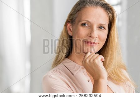 Portrait of a senior woman thinking with hand on chin and looking away. Mature smiling woman feeling happy. Thoughtful retired woman planning her future. Vision concept.