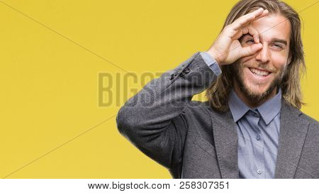 Young handsome business man with long hair over isolated background doing ok gesture with hand smiling, eye looking through fingers with happy face.