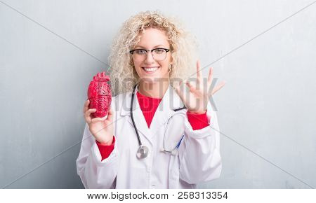 Young blonde cardiologist doctor woman over grunge grey wall holding red heart doing ok sign with fingers, excellent symbol