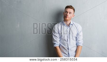 Young redhead business man over grey grunge wall making fish face with lips, crazy and comical gesture. Funny expression.