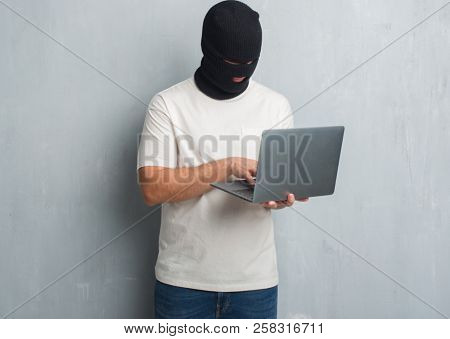 Young caucasian hacker man over grey grunge wall doing cyber attack using laptop with a confident expression on smart face thinking serious