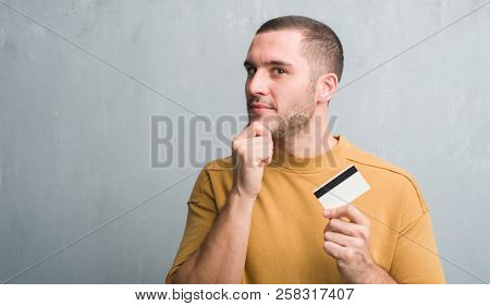 Young caucasian man over grey grunge wall holding credit card serious face thinking about question, very confused idea