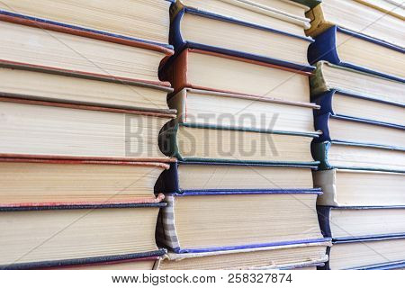 Stack of Used Old Books Background, Books of Different Thickness and Color, Many Books Piles in the School Library, Pile of Old Books Stacked on Top of Each Other, Education Background, Back to School