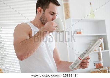 Joven tomando café mientras lee las noticias en su cocina