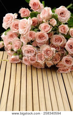 branch rose on wooden board mat