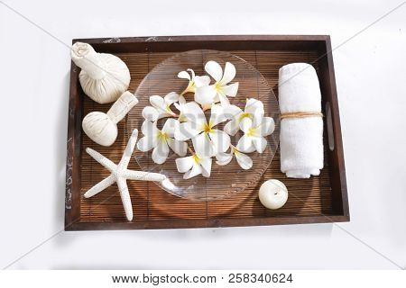 Many white frangipani in bowl,bottle oil, candle, towel, herbal, ball on basket