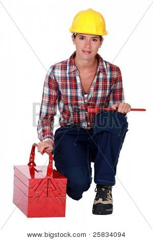 craftswoman holding a spanner and a toolbox