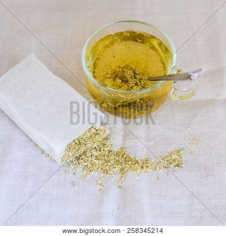 White Herbal Tea With Dried Chamomile Flowers, Tea In Glass Cup With Spoon Near White Paper Bag And