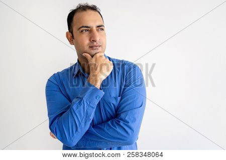 Pensive Indian Man Touching Chin And Looking Away. Handsome Guy Thinking. Contemplation Concept. Iso