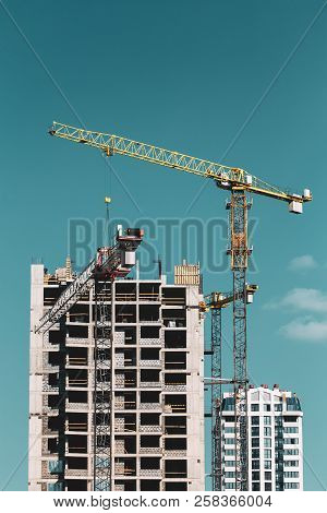 Construction Crane Is Involved In The Construction Of A New Multi-storey Residential Building. Sunny