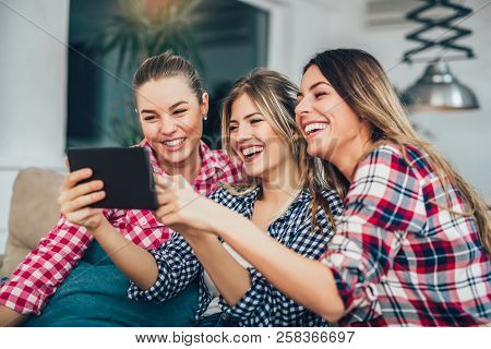 Three Best Friends Using Digital Tablet Together. Women Sitting On Sofa Having Fun Surfing On The In
