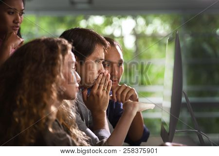 Group Of Young Businesspersons Looking Intently At The Screen With Shock Anxious And Worried Express