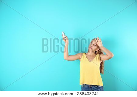 Young Woman Suffering From Heat On Color Background With Copy Space Text. Air Conditioner Malfunctio