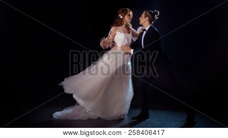 Romantic mysterious portrait of bride and groom. Low key, guy and girl hurry to hug. Man and woman, wedding dress. poster