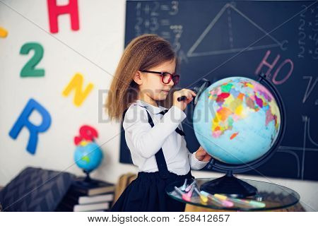 Portrait Of A Beautiful Young Schoolgirl Girl Exploring The Globe Through A Magnifier. Day Of Knowle
