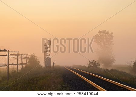 Golden Sunrise With Railroad Tracks And Telephone Poles