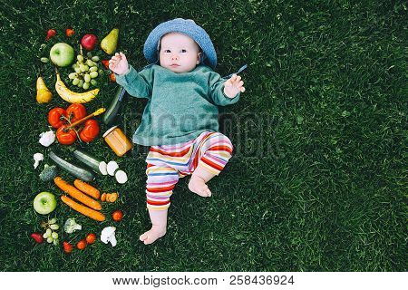 Baby In Colorful Clothes Trying Food And Frame Of Different Fresh Fruits And Vegetables On Green Gra