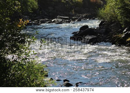 A Clear, Flowing Stream Winds Its Way Through A Canyon In The Colorado Rockies.