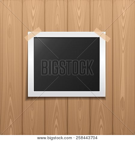 Photo Pasted By An Adhesive Tape To A Board. Realistic Photo Frame Placed On A Wooden Background. Te