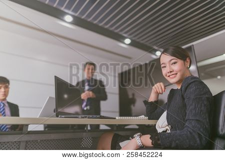Young Asian Businesswoman Sitting At A Boardroom And Smiling At The Camera In A Boardroom With Colle