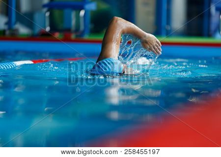 Photo of athletic man in blue cap swimming in pool