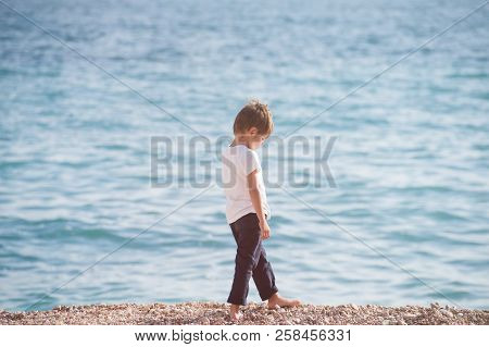 Pensive Sad Caucasian Lonely Small Boy Walking Along Sea Coast Beach In Autumn Season