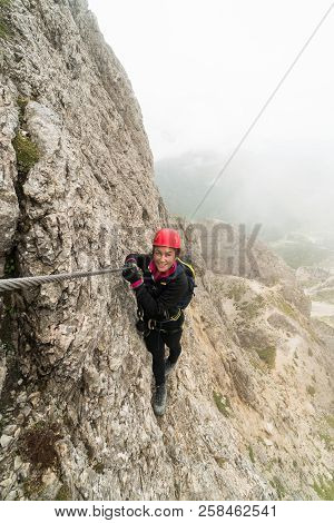 young attractive female mountain climber on a steep and exposed Via Ferrata in Alta Badia in the South Tyrol in the Italian Dolomites poster