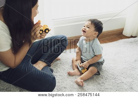 Happy Loving Family. Mother Playing With Her Baby In The Bedroom. Pretty Woman Holding A Newborn Bab