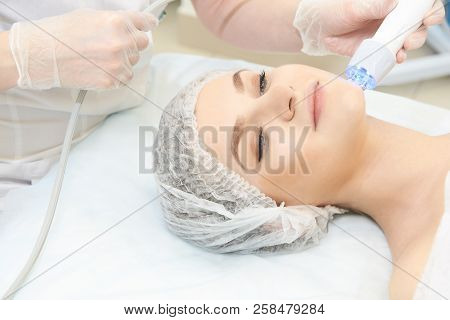 Microcurrent Facial Dermatology Procedure. Model. Aesthetic Radiofrequency Treatment. Micro Current