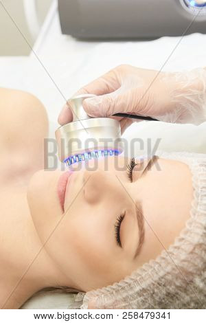Microcurrent facial dermatology procedure. Model. Aesthetic radiofrequency treatment. Micro current cosmetology massage. poster