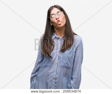 Young beautiful hispanic business woman making fish face with lips, crazy and comical gesture. Funny expression.
