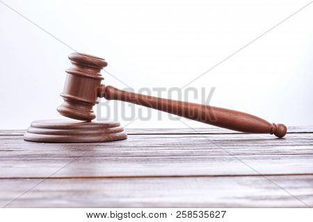 Judge Gavel On Wooden Table. Wooden Gavel Over White Background. Justice And Punishment Concept.