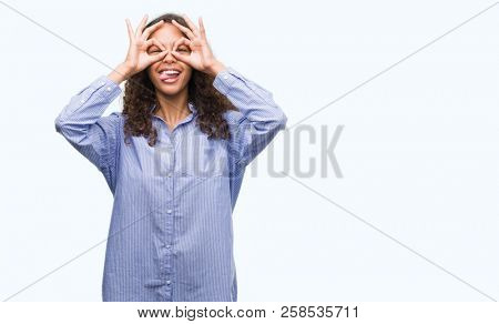 Young hispanic business woman doing ok gesture like binoculars sticking tongue out, eyes looking through fingers. Crazy expression.