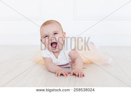Smiling Infant Baby 6 Month Old. Cute Little Girl In Modern Clothes. Happy Baby Looking At Camera
