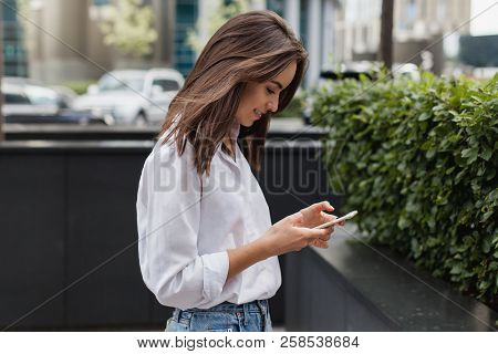Happy Pretty Brunette Girl Using Mobile Phone Near Office, Beautiful Woman Browsing Phone And Doing