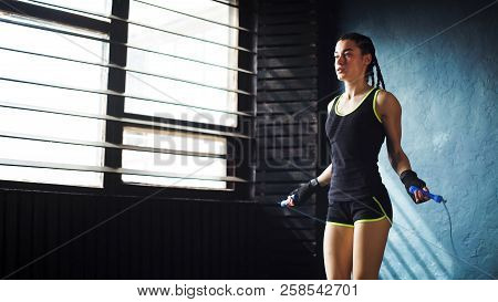 Young Serious Female Boxer In Wrapped Hands Warming Up, Jumping On Skipping Rope Free Space, Copyspa