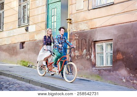 Young Couple, Handsome Bearded Man And Pretty Blond Woman In Glasses Riding Together Tandem Double R