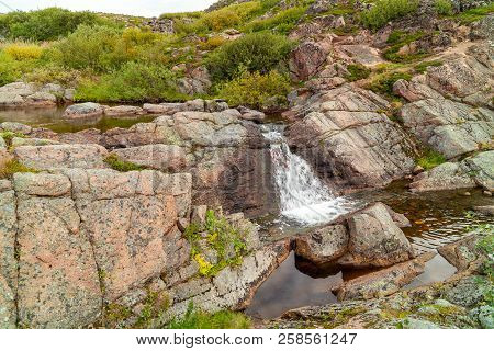 Sream Connecting Two Lakes In The Tundra Of The Kola Peninsula In Inclement Weather, Green Moss And