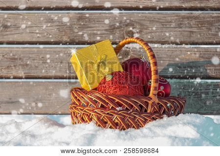 Christmas Gift Box And Christmas Decorations In Basket On Snow. Selective Focus.