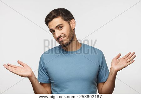I Don't Know. Portrait Of Young Confused Man In Blue T-shirt Standing And Shrugging Shoulders, Sprea