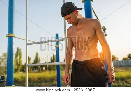 Horizontal Image Of Athlete Fitness Muscular Male Relaxing After Training On Sports Ground Outdoors.