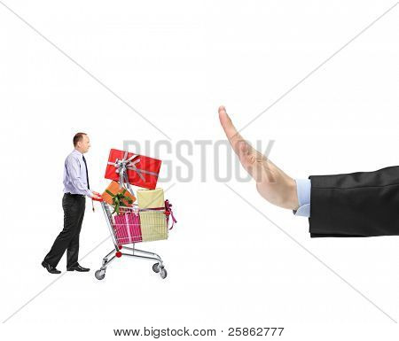 Man pushing a shopping cart full with presents and a hand gesturing stop isolated on white background