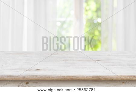 Wooden Empty Board In Front Of Blurred Curtained Window Background