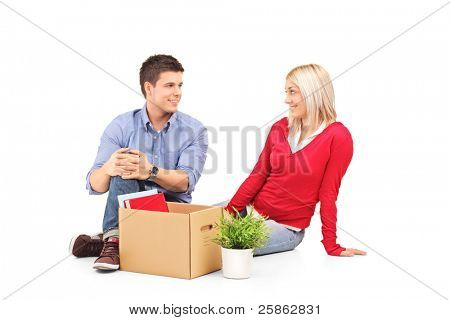 Young man with his woman sitting and resting after moving into a new home isolated on white