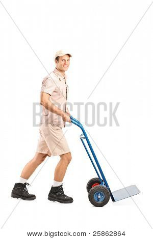 Full length portrait of a manual worker pushing an empty handtruck isolated on white background