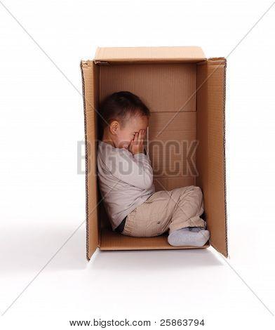 Sad Little Boy Hiding In Cardboard Box