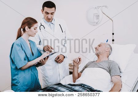 Clinic And Doctor With Patient. Old Man In Hospital. Clinic And Doctor With Patient. Old Man In Hosp