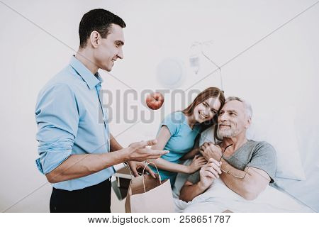 Man And Girl With Old Man In Hospital. Rehabilitation In Clinic. Food For People In Hospital. Man An