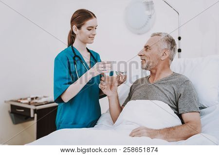 Therapy For Aged Man. People In Clinic. Professional Young Nurse. Interior In Hospital. White Room W