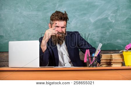 Examiner Cunning Face Sit At Table Chalkboard Background. School Exam Concept. Examinator Bearded Te